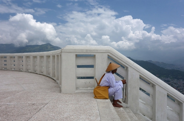 A man counts prayer beads at the top of World Peace Monument Pokhara in Nepal on July 8, 2014. (drburtoni/Flickr)
