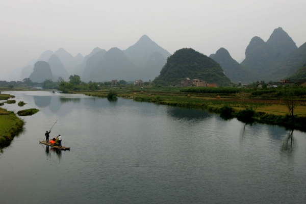 A villager rows a bamboo raft carrying tourists for sightseeing on the Lijiang River in Yangshuo County of Guilin, Guangxi Zhuang Autonomous Region, South China. (Photo by China Photos/Getty Images)