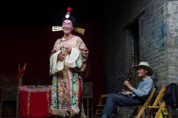 A man in costume smiles at the camera as his friend holding an erhu, a Chinese violin, looks on in Guangxi, China on April 26, 2015. (cotaro70s/Flickr)