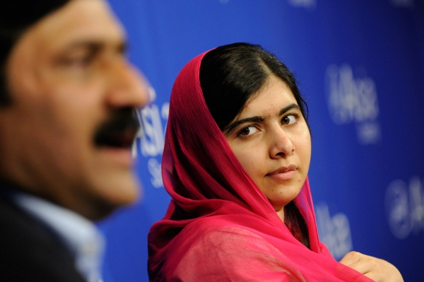 Malala Yousafzai listens as her father, Ziauddin Yousafzai, addresses attendees at Asia Society on Saturday, September 26. (Elena Olivo/Asia Society)