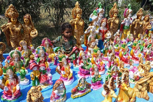 An Indian child, the daughter of a roadside vendor, sits among statues of Hindu Goddess Lakshmi, who represents wealth, at a stall ahead of Diwali in Hyderabad on October 21, 2014. (Noah Seelam/AFP/Getty Images)