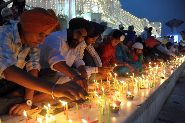Indian Sikh devotees light candles during Diwali at the illuminated Golden Temple in Amritsar, India on October 23, 2014. (Narinder Nanu/AFP/Getty Images)