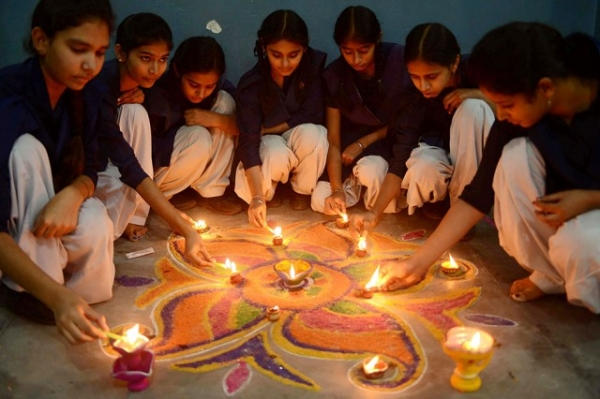 Indian schoolgirls light candles as they sit near a rangoli (a decorative design with sacred overtones) made out of colored powder during a pre-Diwali celebration at a school in Amritsar on November 12, 2012. (Narinder Nanu/AFP/Getty Images)