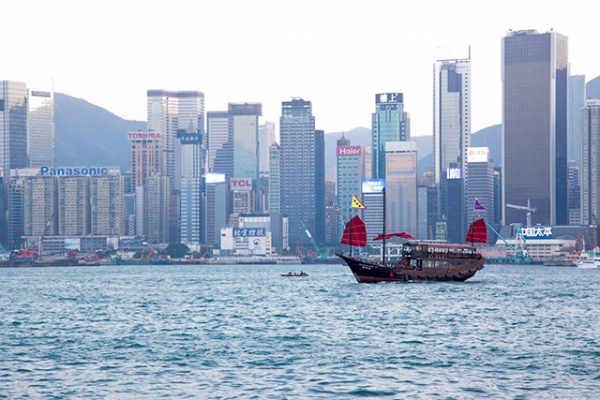 A junk boat with dark, red sails glides past the tall buildings of Hong Kong Island on November 28, 2015. (Tahiat Mahboob)