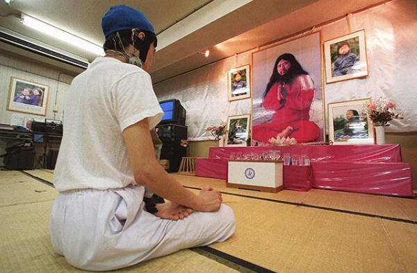 An Aum Shinrikyo follower meditates before portraits of leader Shoko Asahara and his two sons posted on an altar at a seminary of a Tokyo building on August 11, 1999. (Toru Yamanaka/AFP/Getty Images)