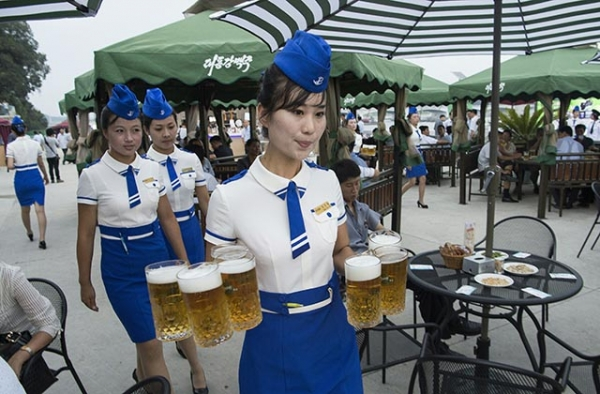 A waitress carries jugs of beer to guests before the opening of the Pyongyang Taedonggang Beer Festival on the banks of the Taedong river in Pyongyang on August 12, 2016. (Kim Won-jin/AFP/Getty)