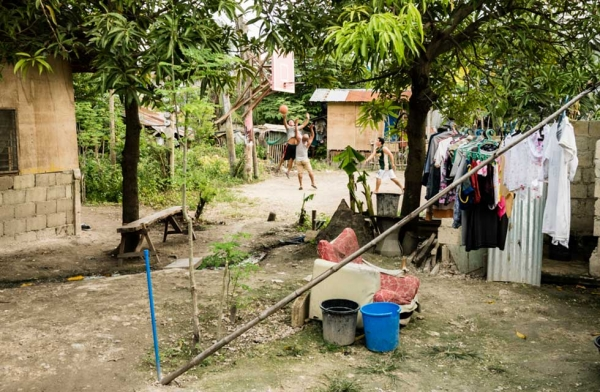 Sunday is Wash Day and hoops for the men. There are no water mains in this village. Water is collected from deep wells by manual water pumps. Cebu, Philippines. (Richard James Daniels)