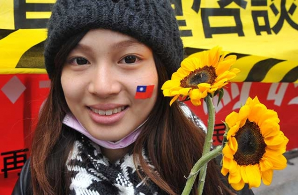 An activist holds sunflowers and wears a sticker of Taiwan's national flag on her face in support of student protesters occupying the parliament building in Taipei on March 21, 2014. (Mandy Cheng/AFP/Getty)