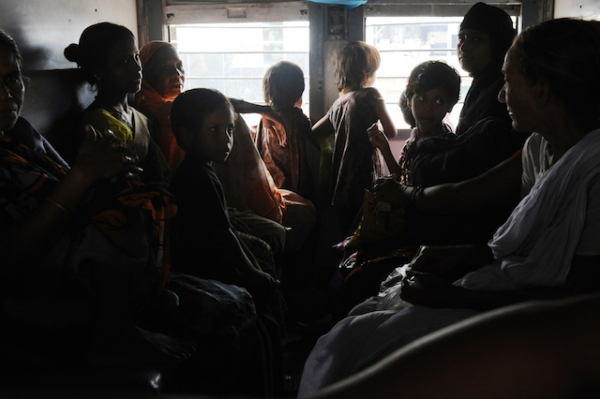 Indian women and children wait inside a darkened train carriage at a railway station in New Delhi on July 31, 2012. (Roberto Schmidt/AFP/GettyImages)