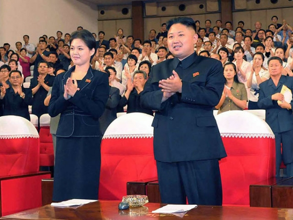 North Korean leader Kim Jong Un (C), accompanied by a young woman later confirmed as his wife Ri Sol-Ju (L), enjoying a performance by the newly organized Moranbong band in Pyongyang on July 6, 2012. (KNS/AFP/GettyImages)