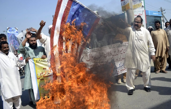 A Pakistani United Citizen Action demonstrator holds a burning US flag during a protest in Multan on October 25, 2012 against the US drone attacks in Pakistani tribal areas. (S.S. Mirza/AFP/Getty Images)