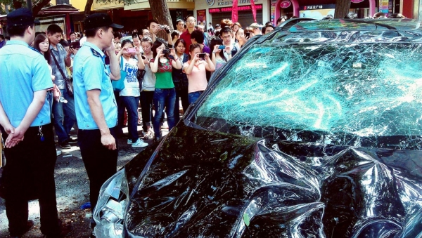 People take pictures of a Japanese car damaged during a protest against Japan's 'nationalizing' of the disputed Diaoyu Islands, also known as Senkaku Islands in Japan in Xi'an, northwest China's Shaanxi province, on September 15, 2012. (AFP/GettyImages)