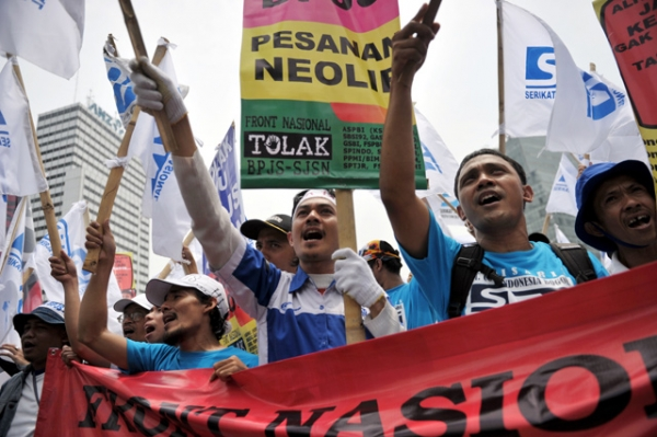 Indonesian workers display placards during a rally in Jakarta on Nov. 21, 2012, when thousands of workers took to the streets calling on the government to increase wages and end the practice of outsourcing manpower. (Bay Ismoyo/AFP/Getty Images)