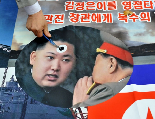 A South Korean activist stabs a pocket knife on a picture of North Korean leader Kim Jong-Un (L) during an anti-North Korea rally near the national assembly in Seoul on March 22, 2013. (Jung Yeon-Je/AFP/Getty Images)