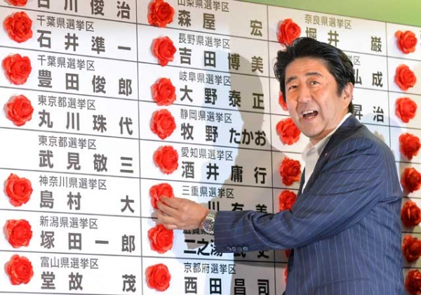 Japan's Prime Minister and President of the Liberal Democratic Party (LDP) Shinzo Abe smiles as he places a red paper rose on an LDP candidate's name to indicate an election victory at the party's headquarters in Tokyo on July 21, 2013. (Kazuhiro Nogi/AFP/Getty Images)