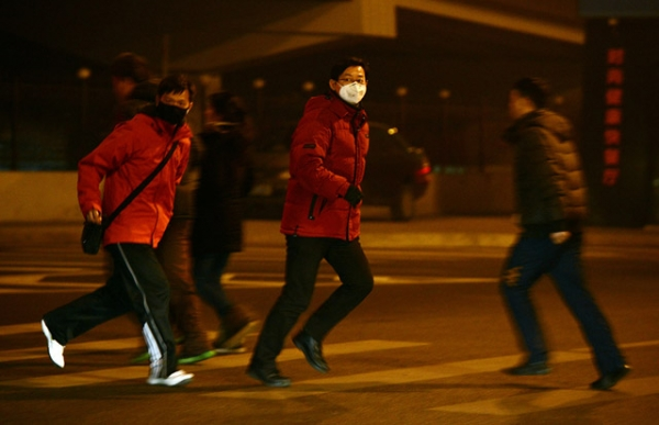 Commuters cross a Beijing street in heavy air pollution, January 30, 2013. On this day, when PM2.5 readings reached a high of 315, according to measurements taken by the U.S. Department of State, Beijing officials urged people to stay indoors. (Mark Ralston/AFP/Getty Images)