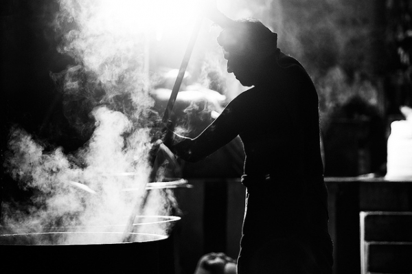 A cook prepares a large feast in giant pots billowing with steam in Tiruvannamalai, India on November 22, 2013. (Vinoth Chandar/Flickr)