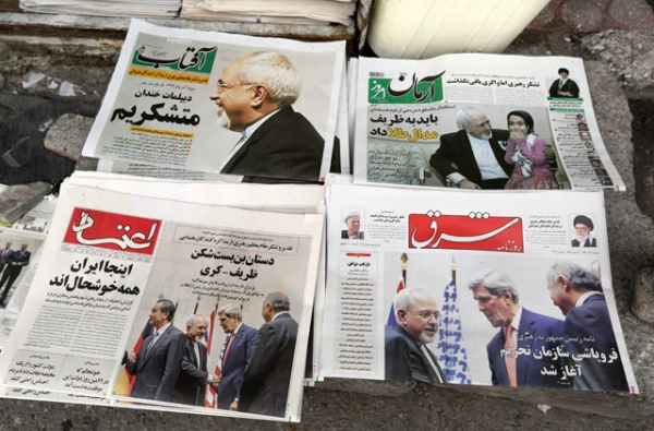 Iranian newspapers headlining the deal made with major powers over Iran's nuclear program are displayed outside a Tehran kiosk on Nov. 25, 2013. Most Iranian newspapers hailed the deal, attributing its relatively swift success to Foreign Minister Mohammad Javad Zarif (top left). (Atta Kenare/AFP/Getty Images)