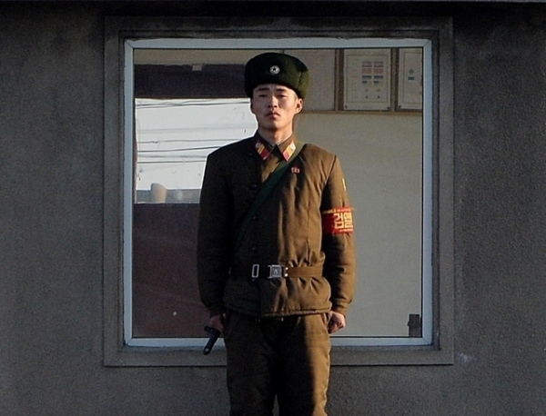 A North Korea soldier stands guard on the banks of the Yalu River which separates the North Korean town of Sinuiju from the Chinese border town of Dandong on the second anniversary of the death of former leader Kim Jong-Il, December 17, 2013. (Mark Ralston/AFP/Getty Images)