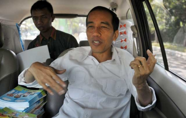 Jakarta governor Joko Widodo, an avowed rock fan, tries some air guitar while traveling by van to a site inspection in Jakarta on Aug. 22, 2013. The charismatic governor is predicted to make a run for Indonesia's presidency in 2014. (Bay Ismoyo/AFP/Getty Images)