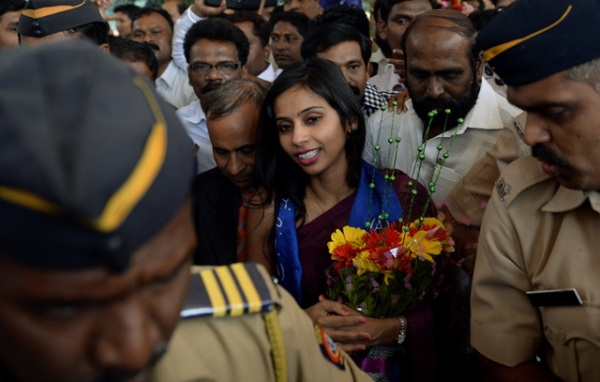 Indian diplomat Devyani Khobragade (CR), accompanied by her father Uttam Khobragade (CL) and surrounded by supporters and policemen, arrives at the domestic airport in Mumbai on January 14, 2014. (Punit Paranjpep/AFP/Getty Images)