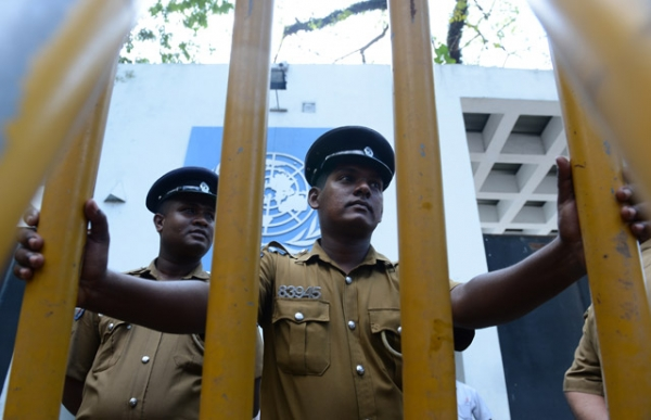 Sri Lankan policemen look on as Tamil pro-government activists take part in a demonstration outside the UN offices in Colombo on March 10, 2014, to protest a proposed US-led UN resolution to investigate Sri Lanka for alleged war crimes. (Lakruwan Wanniarachchi/AFP/Getty Images)