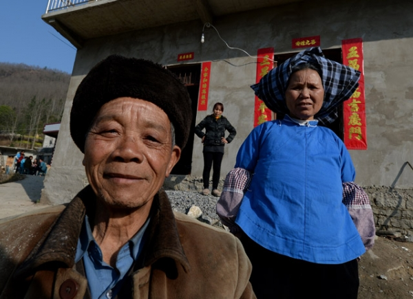 Rural residents pose in front of their new houses near the city of Anshun, Guizhou Province, in February 2014. (Mark Ralston/AFP/Getty Images)