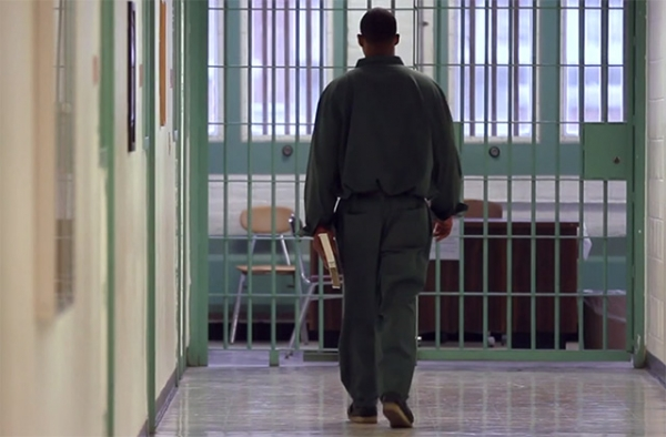 Inmate in New York State carries a book through a prison corridor. (Bard Prison Initiative promotional film screen grab; Winton/duPont Films)