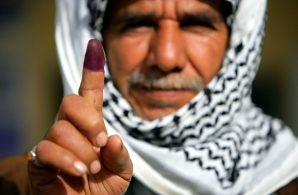 An Iraqi man in Najaf displays his finger to the camera on January 30, 2005 in Najaf, Iraq. The purple dye indicates that he has just voted in Iraq's first elections. (Brent Stirton/Getty Images)
