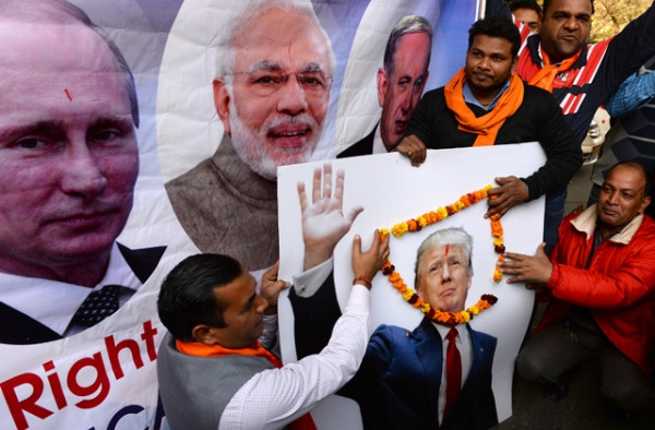 Right-wing activists of India's Hindu Sena party pose with a poster of Russian President Vladimir Putin, (L), Indian Prime Minister Narendra Modi (2L) and US President-elect Donald Trump (R) during an event in New Delhi on January 19, 2017.(Sajjad Hussain/AFP/Getty Images)