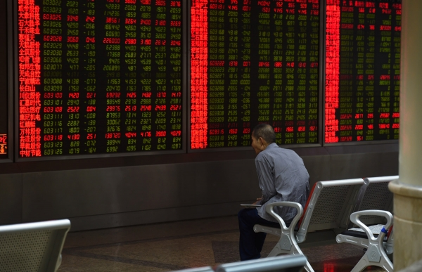 An investor watches stock price movements on a screen at a securities company in Beijing. (Greg Baker/AFP/Getty Images)