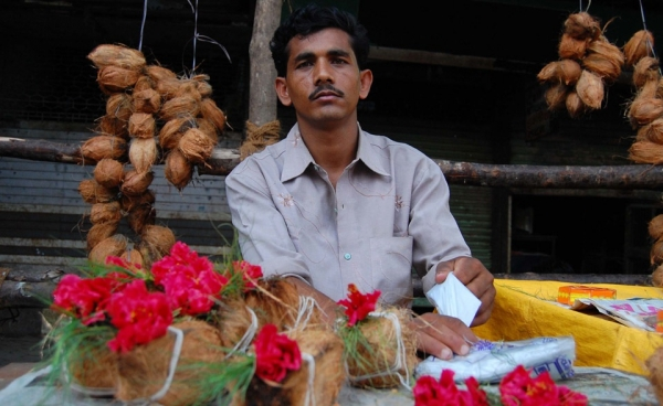A vendor sells flowers and coconuts outside a temple in Mumbai. (Angeline Thangaperakasam and Michael Newbill/Asia Society India Centre)