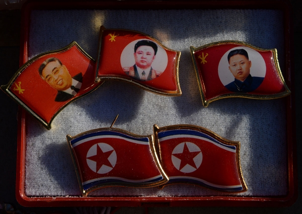 Badges featuring Kim Il Sung, Kim Jong Il, and Kim Jong Un