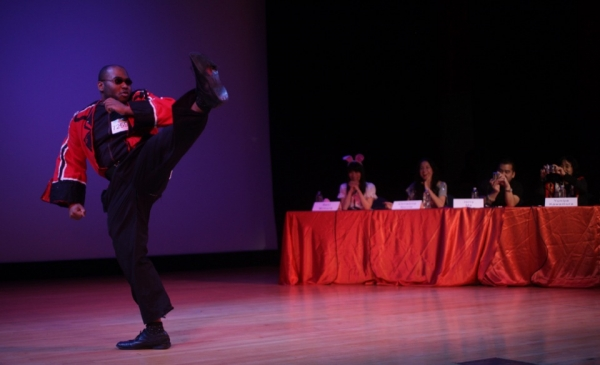 Clif Francisoie strikes a high kick as the judges enthusiastically look on. (David Barreda/Asia Society)