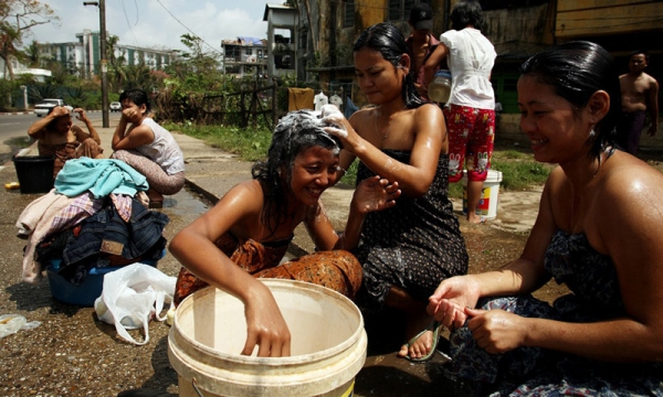 Women use a bucket to cleanse themselves on May 8, 2008 in downtown Yangon. (Chumsak Kanoknan/Getty Images)