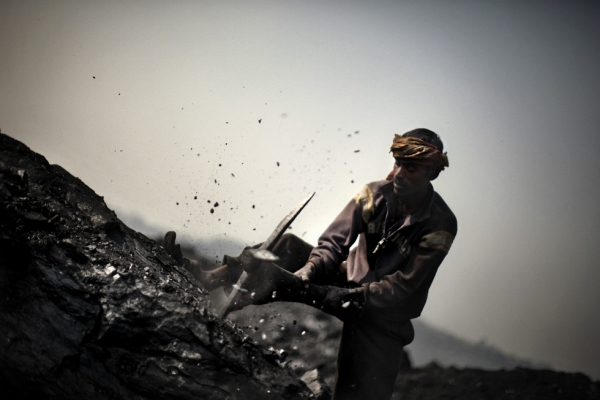 A miner breaks up a large piece of coal. (Erik Messori)