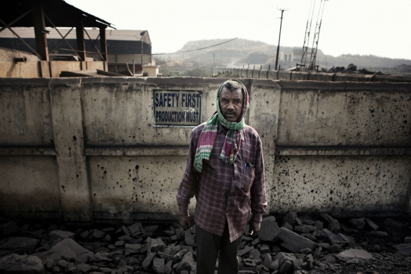 A miner at the entry of a state-owned mine in Jharia. (Note the sign.) (Erik Messori)