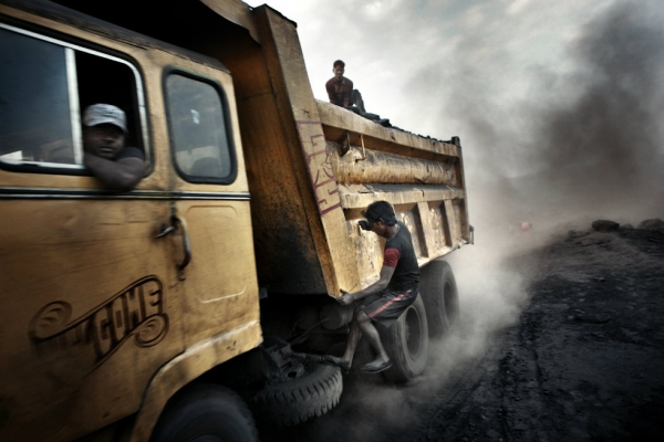 Teenagers jump onto moving trucks, risking their lives to steal a few lumps of coal for the black market. (Erik Messori)