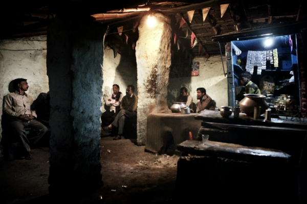 Miners sip on chai after work in the only public place in the village. (Erik Messori)