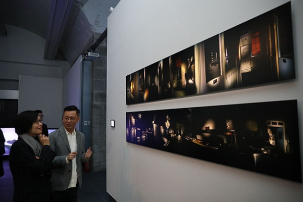 Curator Dominique Chan explains the meaning of Enoch Cheung's Secret Dialogue: About Children Hospital – Night No. 1-7 to Florence Hui.