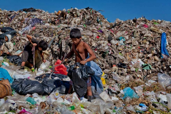 Three refugee children work together at the dump in Mae Sot, Thailand. The child on the left is just seven years old and recently received a pair of gumboots. (Jacques Maudy)