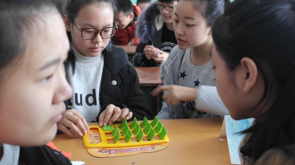 "Students at Mudanjiang Number 2 High School, Heilongjiang Province, use their language skills to play the game ""Guess Who?"" during the English Winter Immersion Camp. (Debora L. Nicholson)"