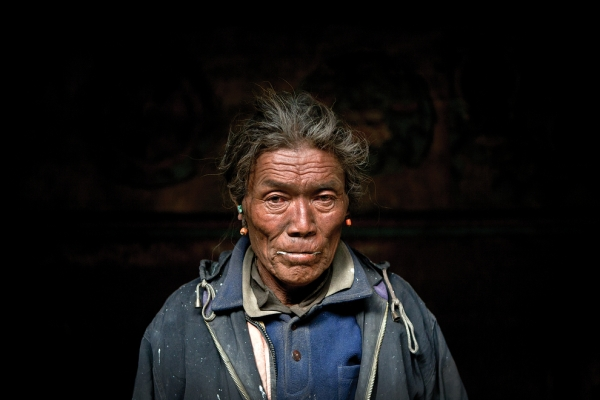 The winter monastery keeper stands for a portrait in the main hall of the monastery in Tetang. (Taylor Weidman)