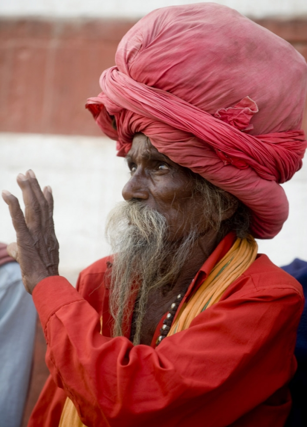 A bearded man in a red turban uses his hands to express himself in Varanasi, India on November 23, 2009. (Nancy A. Scherl)