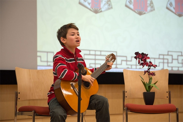 "Contestant from Champion Learning Academy performing a Chinese poem ""Lan Hua Cao"" with guitar. (North Carolina Public Schools)"