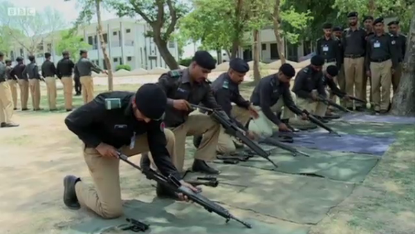 Pakistani police officers load their weapons. (BBC Urdu)
