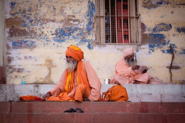 Two venerable Hindu men almost seem to be mirror images of each other on the steps of a building in Varanasi, India on March 17, 2012. ([ changó ]/Flickr)