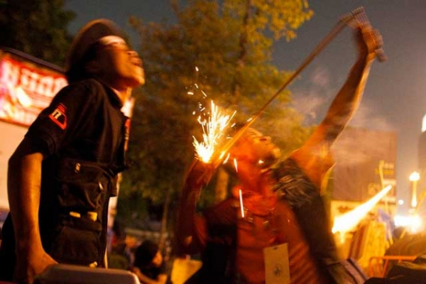 Red shirt protestors use a sling shot to launch a firecracker at Thai security forces from inside their encampment on May 13, 2010 in Bangkok. (Athit Perawongmetha/Getty Images)