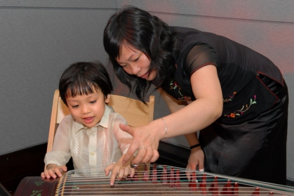 An aspiring musician plays the guqin, a Chinese zither. (Elsa Ruiz/Asia Society)