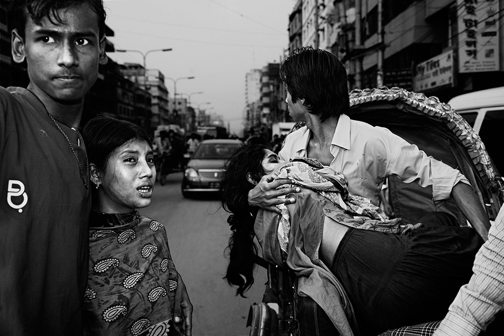 Co-workers rush those injured by the boiler explosion at Pacific Garments Factory to healthcare clinics in Dhaka. (Gazi Nafis Ahmed)